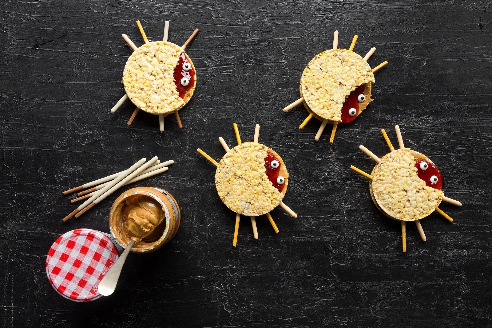 Peanut butter (or nut butter) and jam CORN THINS slices in the shape of spiders