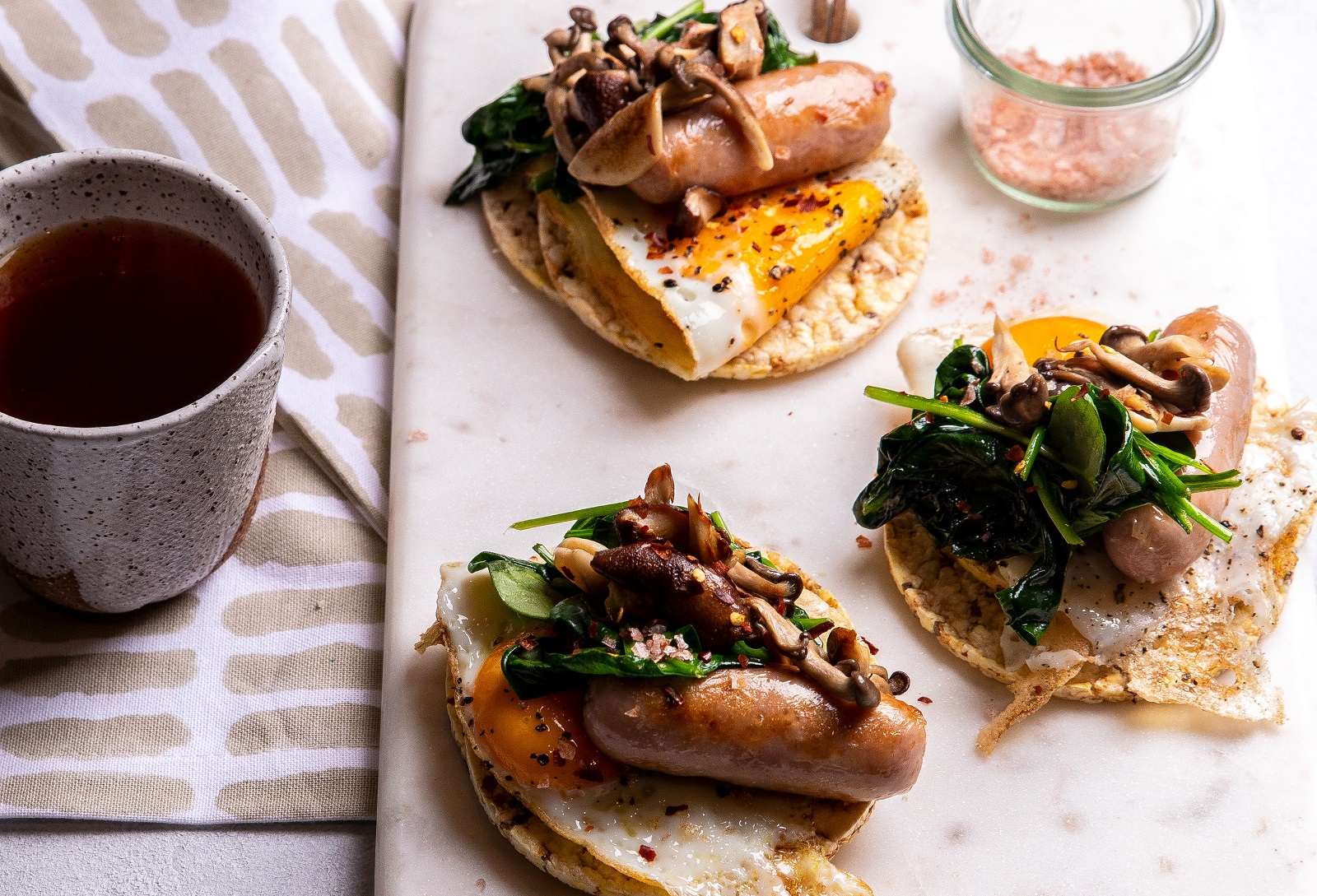 A big breakfast of Fried Egg, Sausage, Mushroom & Spinach on Corn Thins slices