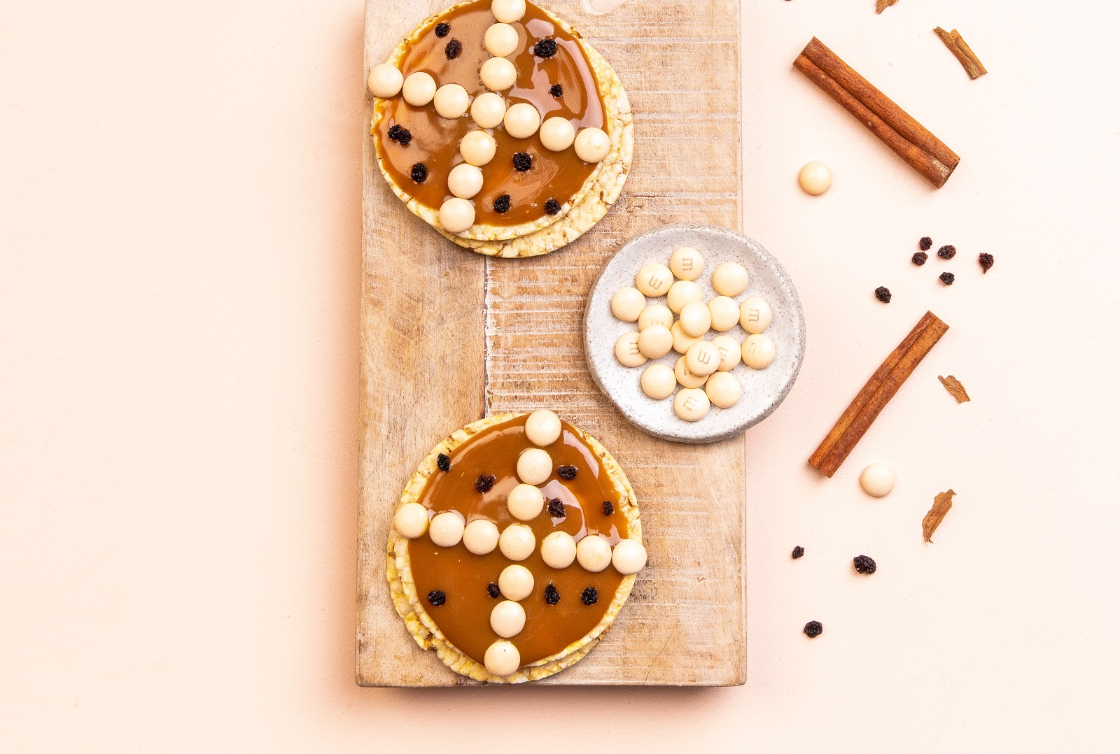 Hot Cross Bun version of Corn Thins. Caramel spread, white M&Ms + currants on Corn Thins slices